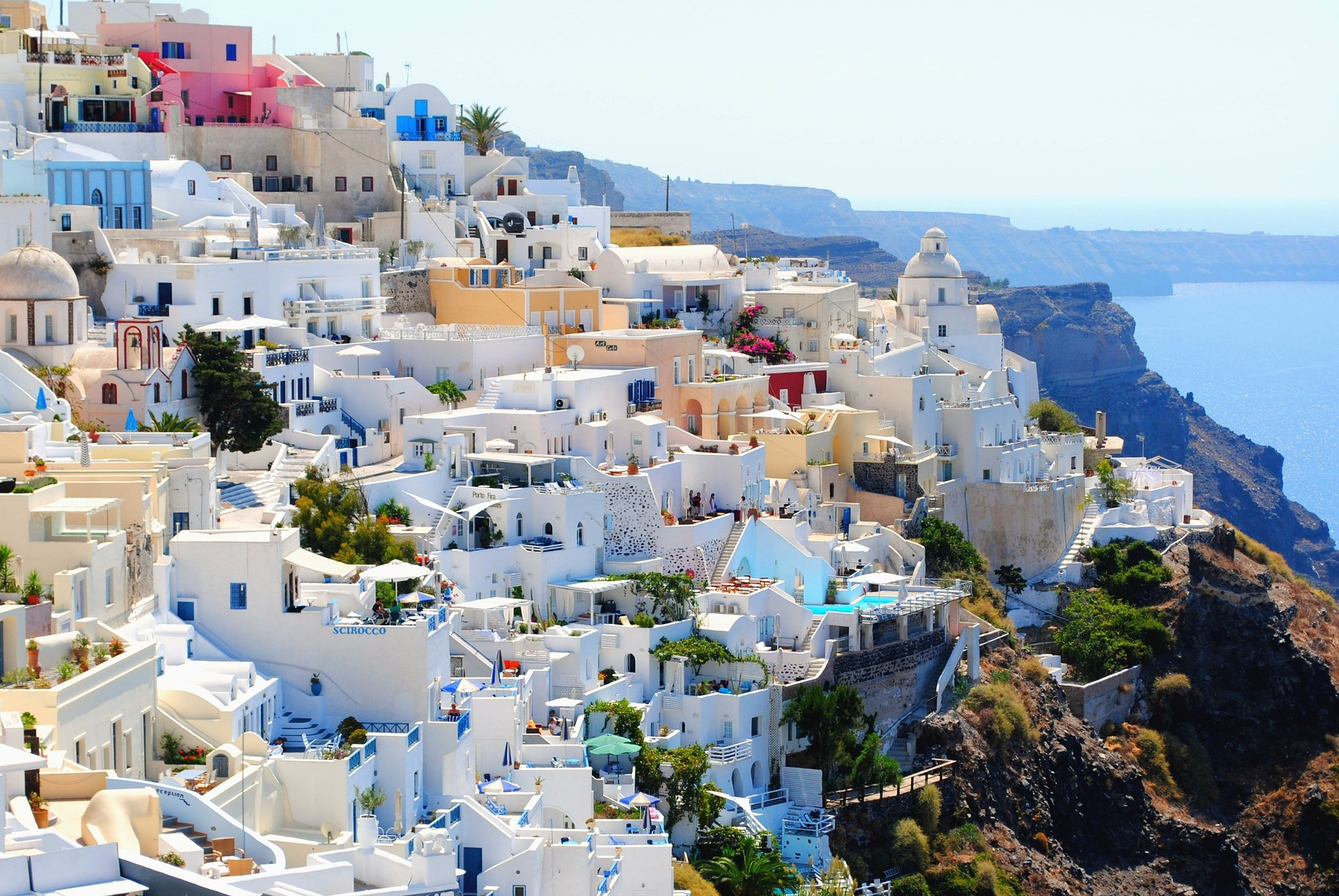 white washed buildings of Santorini on the cliffside with ocean below