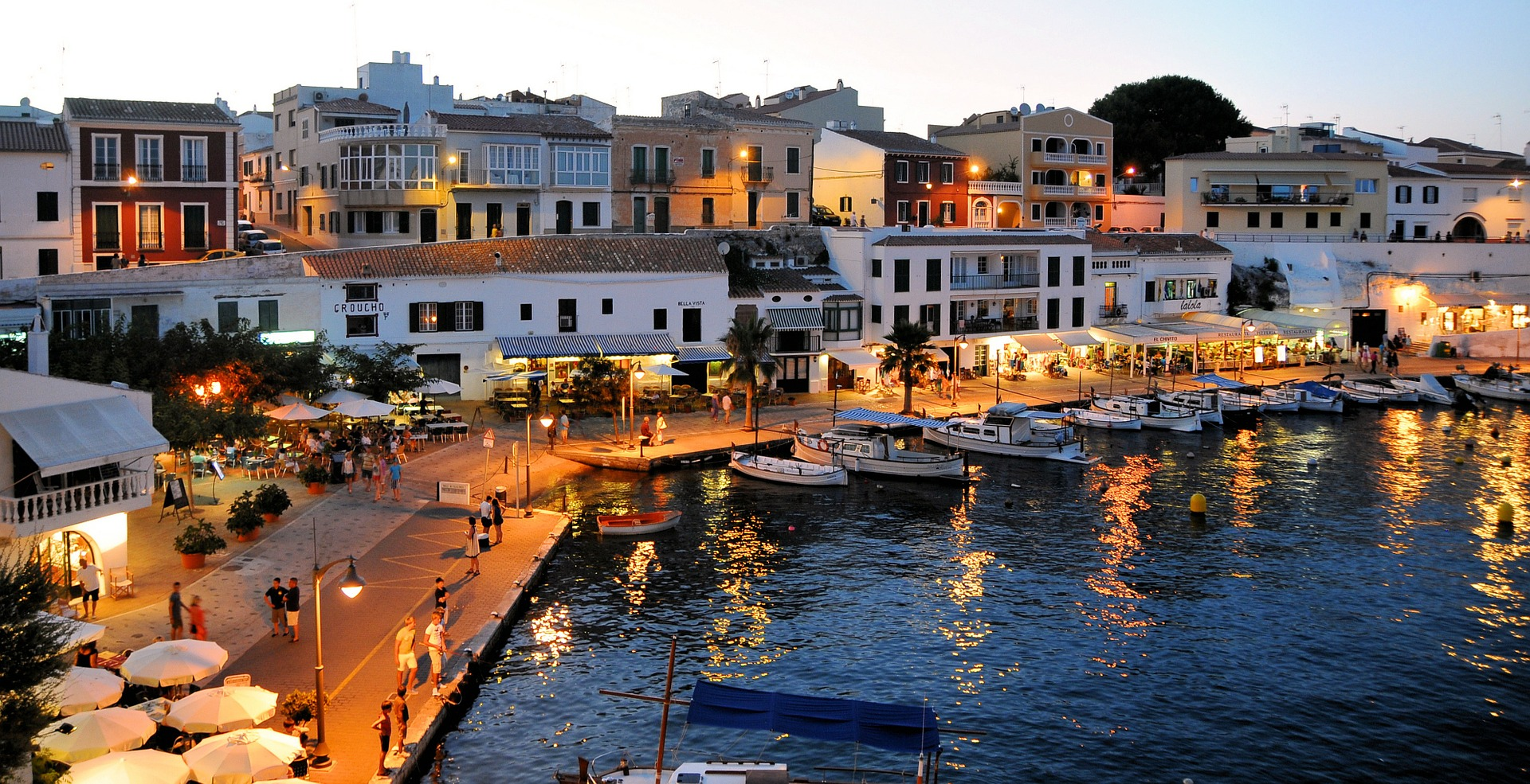 evening shot of harbour in Menorca with lights on the boardwalk and boats at dock