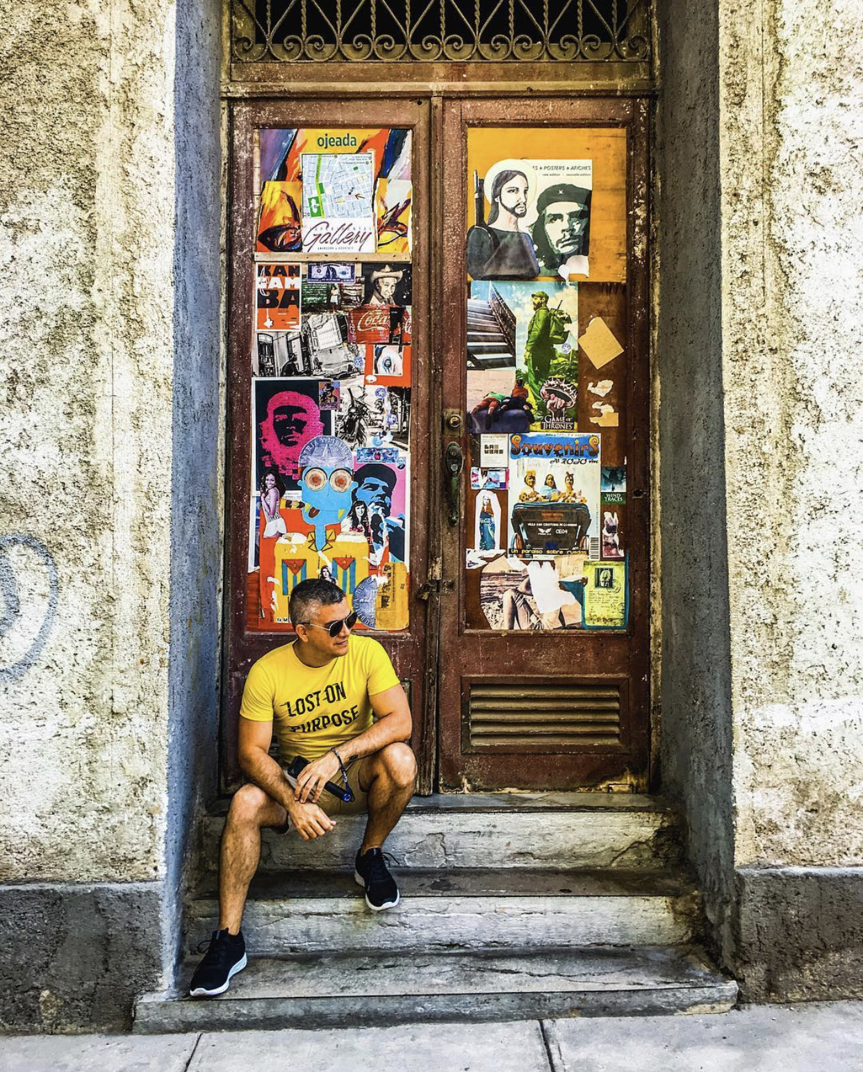 Aruban travel content creator Hyro Oduber sits in front of old doors covered in posters