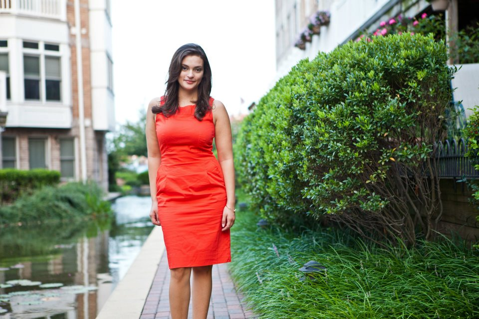Jen Ruiz in bright red dress standing along side the river on one side and greenery on the other