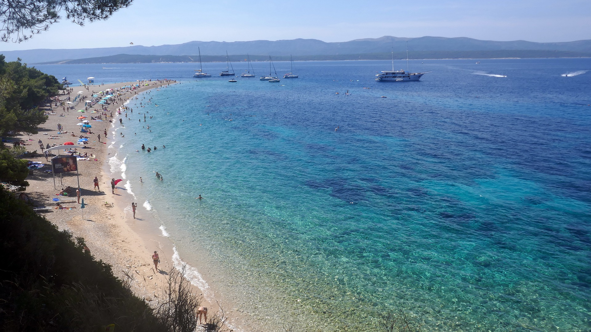 sandy and pebble beach in Croatia with boats at anchor in background