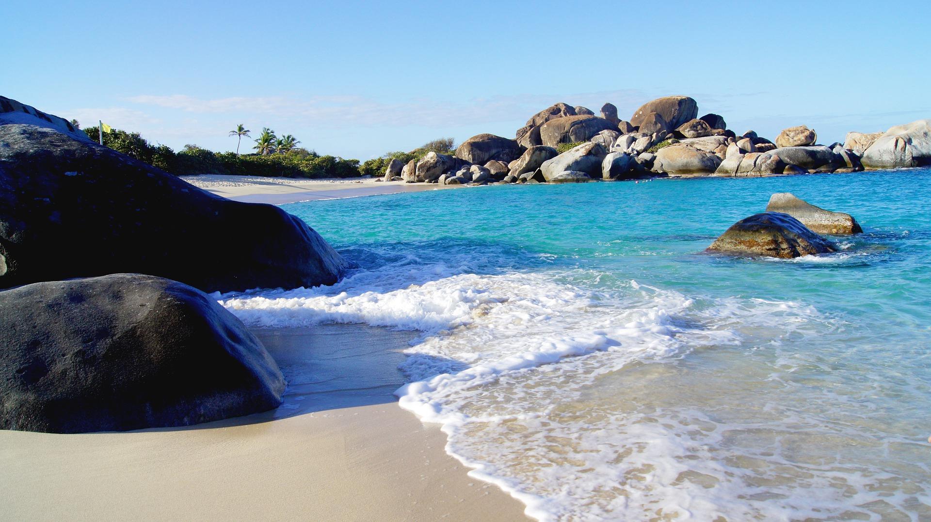 surf washing up on sandy beach in Virgin Gorda with rocks along the beach