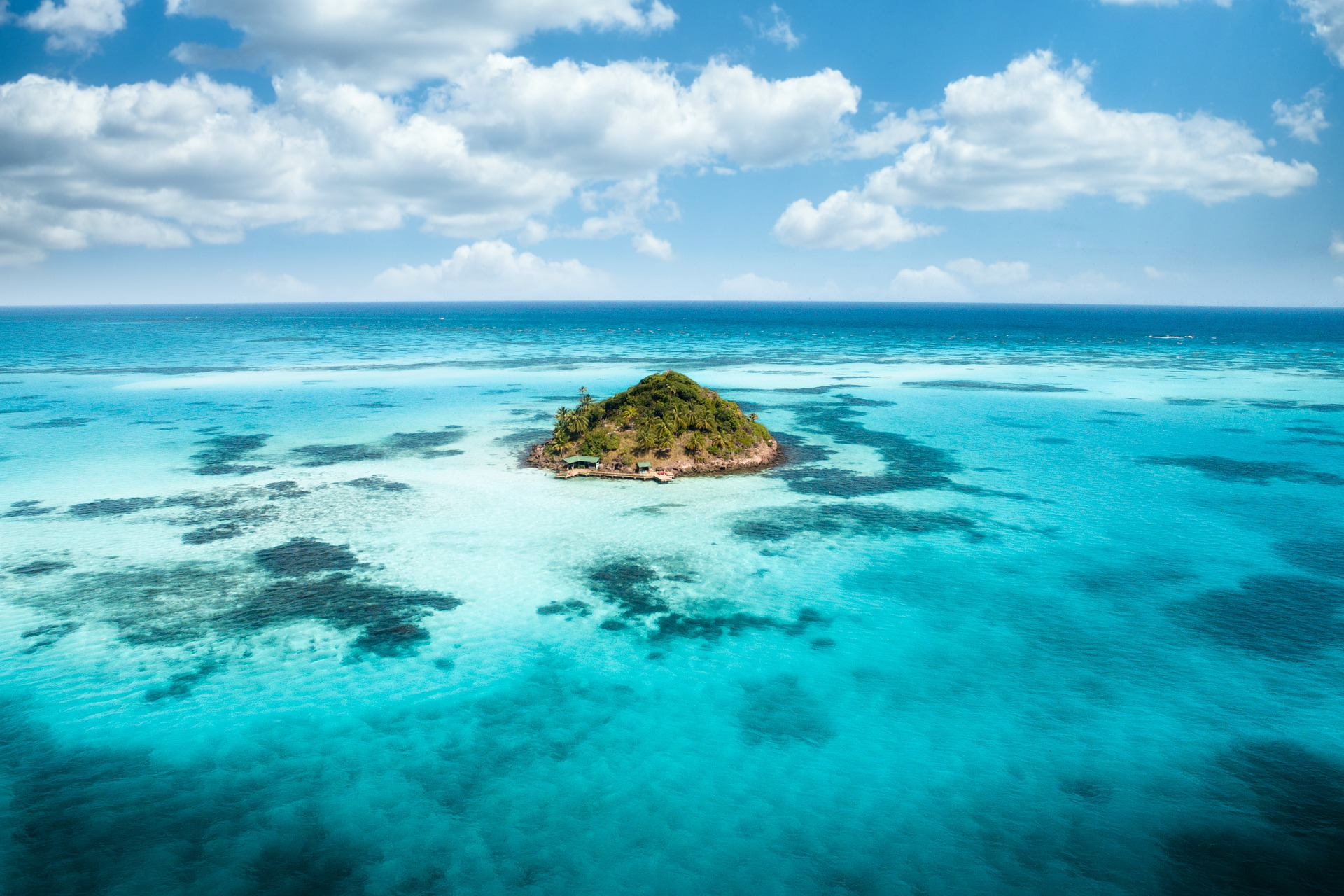 aerial of remote island in the middle of turquoise blue waters with reefs surrounding