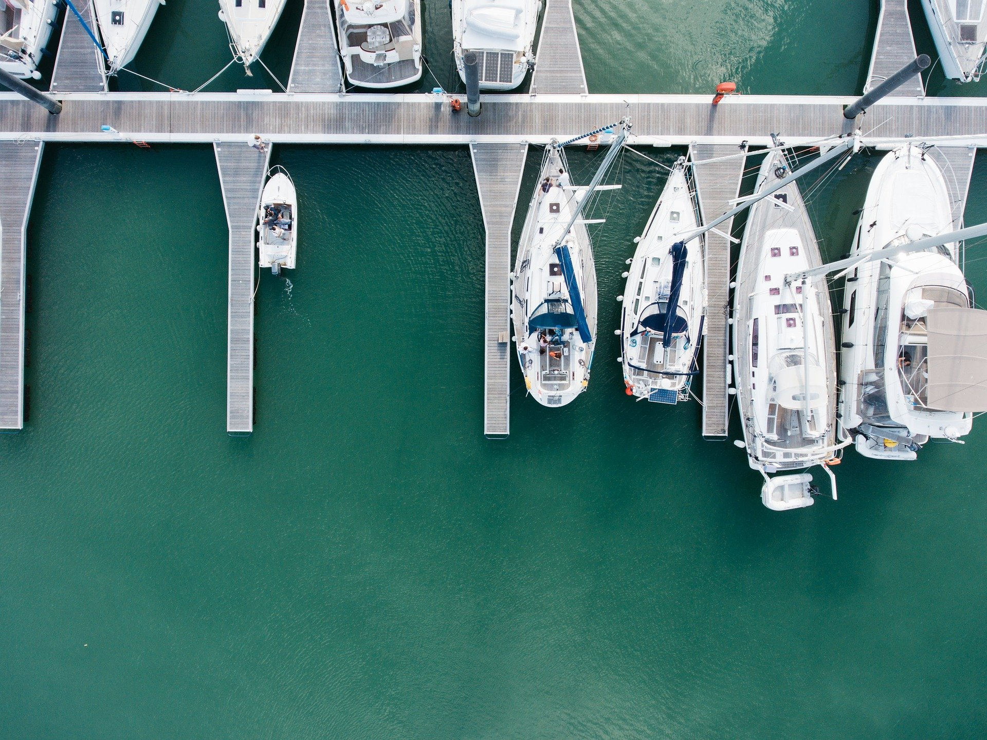aerial shot of yachts in marina with teal water