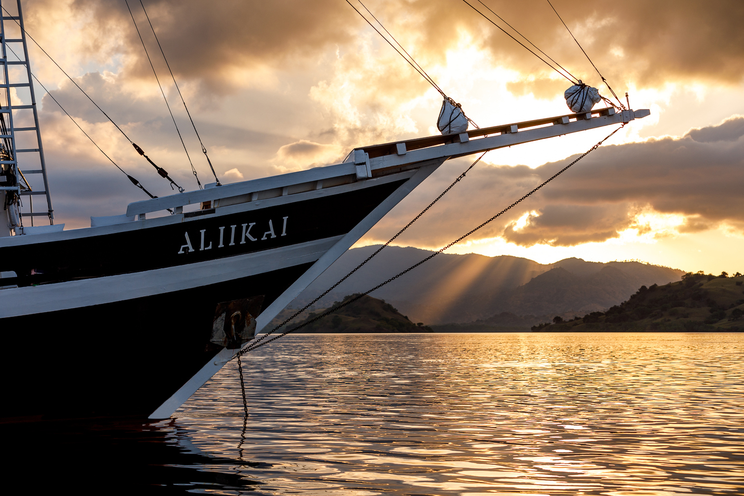 bow of Aliikai yacht with sunset in the background